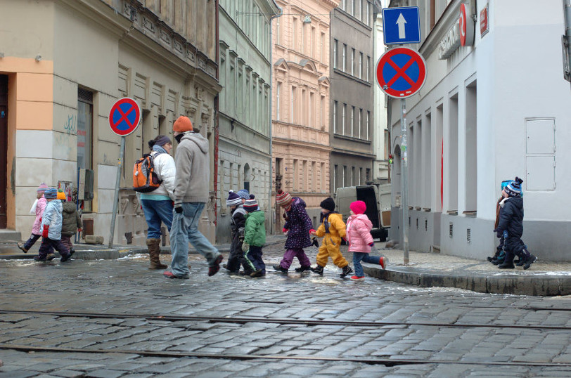 children bundled in coats viewed crossing a street in prague, chzech republic.